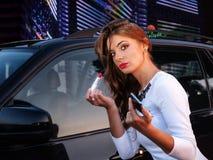 Den unga kvinnan sätter läppstift reflekteras i bildörren Royaltyfri Fotografi