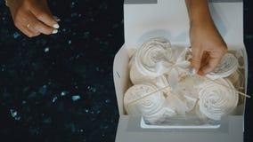 Den unga kvinnan sätter marshmallower med pinnar i kartong inomhus Hon viker trevligt vit flyg- läckerhet lager videofilmer