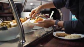 Den unga kvinnan sätter mat på en platta på en matdomstol royaltyfri foto
