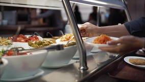 Den unga kvinnan sätter mat på en platta på en matdomstol arkivfoton