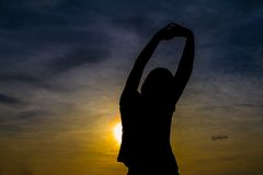 Den unga kvinnan sätter in på över soluppgång Royaltyfri Bild