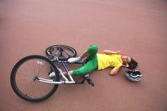 Den unga kvinnan sårade under att rida en cykel Royaltyfri Fotografi