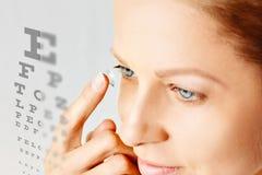 Den unga kvinnan s?tter kontaktlinsen i hennes ?ga Eyewear, synf?rm?ga och vision, ?gonomsorg och h?lso-, oftalmologi- och optome royaltyfria foton