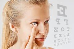 Den unga kvinnan s?tter kontaktlinsen i hennes ?ga Eyewear, synf?rm?ga och vision, ?gonomsorg och h?lso-, oftalmologi- och optome royaltyfri bild