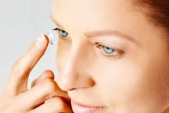 Den unga kvinnan s?tter kontaktlinsen i hennes ?ga Eyewear, synf?rm?ga och vision, ?gonomsorg och h?lso-, oftalmologi- och optome arkivfoton