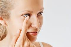 Den unga kvinnan s?tter kontaktlinsen i hennes ?ga Eyewear, synf?rm?ga och vision, ?gonomsorg och h?lso-, oftalmologi- och optome arkivbilder