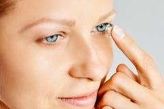 Den unga kvinnan s?tter kontaktlinsen i hennes ?ga Eyewear, synf?rm?ga och vision, ?gonomsorg och h?lso-, oftalmologi- och optome royaltyfri foto