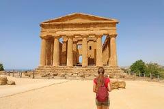 Den unga kvinnan ser den Concordia templet i dalen av templen Agrigento, Sicilien Handelsresandeflickan besöker grekiska tempel i arkivfoton