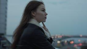 Den unga kvinnan ser framåtriktat till aftonstadsscape arkivfilmer