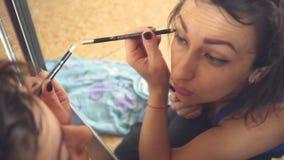 Den unga kvinnan ser henne i spegeln och gör makeup arkivfilmer