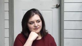 Den unga kvinnan ser någon av kamera och leenden stock video