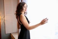 Den unga kvinnan ser ut fönstret Royaltyfria Bilder