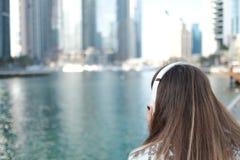 Den unga kvinnan ser vattenkanalen med stora hörlurar över hennes huvud, sikt från baksidan royaltyfri bild