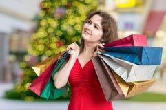 Den unga kvinnan shoppar gåvor för jul shoppar in och bär många påsar Royaltyfria Foton