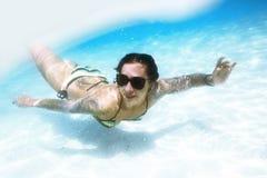 Den unga kvinnan simmar det undervattens- havet arkivbild