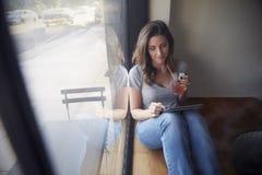 Den unga kvinnan sitter bredvid fönster i kafé genom att använda minnestavladatoren Arkivfoton