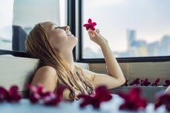 Den unga kvinnan sitter i ett bad med skum, och frangipanien blommar agai Arkivbild