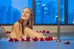 Den unga kvinnan sitter i ett bad med skum, och frangipanien blommar mot bakgrunden av ett panorama- fönster som förbiser skyscra Arkivbild