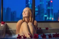 Den unga kvinnan sitter i ett bad med skum, och frangipanien blommar mot bakgrunden av ett panorama- fönster som förbiser skyscra Royaltyfri Fotografi