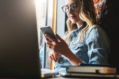 Den unga kvinnan sitter i kafé på fönsterbräda- och brukssmartphonen Hipsterflicka som kontrollerar mejl och att prata, blogging  arkivbilder