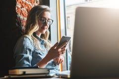 Den unga kvinnan sitter i kafé på fönsterbräda- och brukssmartphonen Hipsterflicka som kontrollerar mejl och att prata, blogging  arkivbild