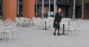 Den unga kvinnan sitter i utomhus- kafé arkivfilmer