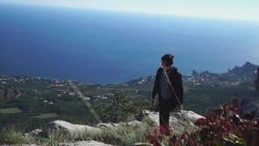 Den unga kvinnan sitter på överst av berget ovanför havet lager videofilmer