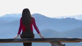 Den unga kvinnan sitter på bänk utanför och blick på det bildmässiga landskapet med berg lager videofilmer