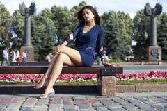 Den unga kvinnan sitter på en bänk Royaltyfria Bilder