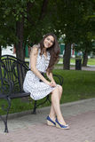 Den unga kvinnan sitter på en bänk Arkivfoton