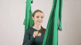 Den unga kvinnan sitter på en hängmatta som ler kvinnan som visar dig att kalla mig tecknet Flyg- aero klipsk konditioninstruktör stock video