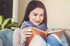 Den unga kvinnan sitter på en soffa och läser en bok arkivbilder