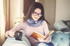 Den unga kvinnan sitter på en soffa och läser en bok, medan rymma en kopp kaffe eller ett te arkivfoto