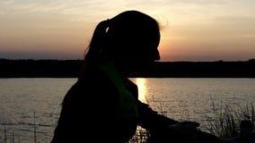 Den unga kvinnan sitter på ett te för sjöbankdrinkar från en termos arkivfilmer