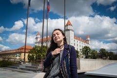 Den unga kvinnan sitter på fyrkant med en sikt på slott royaltyfri fotografi