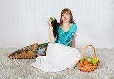 Den unga kvinnan sitter på mjuk matta arkivfoto
