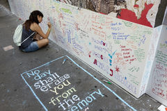 Den unga kvinnan sitter på trottoar nära ground zero och skriver på väggen Fotografering för Bildbyråer