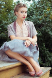 Den unga kvinnan sitter på gammala moment Arkivfoto