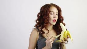 Den unga kvinnan skalar och äter bananen i den vita studien stock video