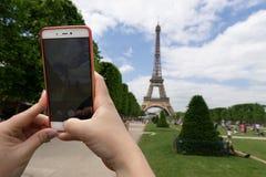 Den unga kvinnan skjuter Eiffeltorn på en mobiltelefon i eftermiddagen med blå himmel och vita moln arkivfoton