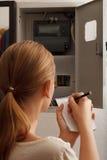 Den unga kvinnan skrivar om de elektriska meterläsningarna Arkivbild