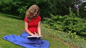 Den unga kvinnan skriver havandeskapdagboken sitter i gräsplan parkerar sommardag stock video