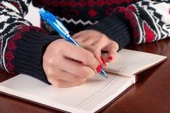 Den unga kvinnan skriver med blyertspennan i anteckningsbok på träskrivbordet royaltyfri bild