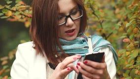 Den unga kvinnan skriver meddelanden i telefonen på en bakgrund av gula sidor, medan gå i hösten, parkerar stock video