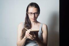 Den unga kvinnan skriver om affär Royaltyfri Foto