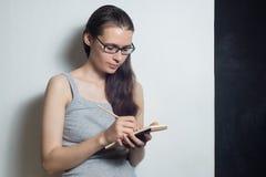 Den unga kvinnan skriver om affär Royaltyfri Fotografi