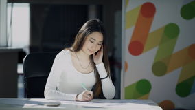 Den unga kvinnan skriver sammanträde på tabellen inomhus stock video