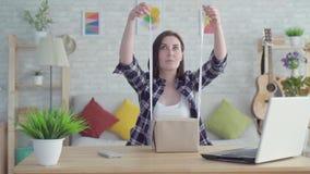 Den unga kvinnan slår in en gåva som sitter på tabellen långsam mo lager videofilmer