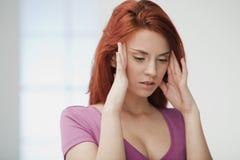 Den unga kvinnan smärtar in. Arkivfoto