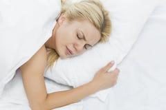 Den unga kvinnan smärtar in att ligga på säng Fotografering för Bildbyråer